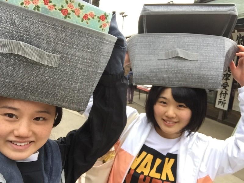 頭に3キロの水をいれた箱を乗せる。左が西岡さん、右が正木さん